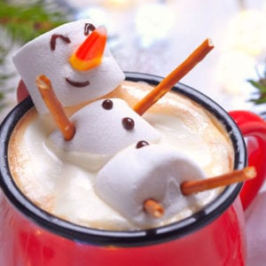 Marshmallows made to look like snowman inside a hot cocoa.