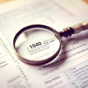 a magnifying glass laying on a 1040 form