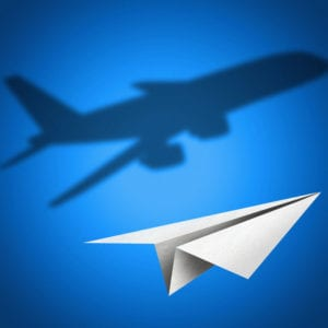 image of a paper plane flying against a blue wall but casting the shadow of a large jet liner