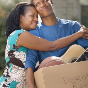 Mother hugging teenage son as he packs for college and he is embarassed