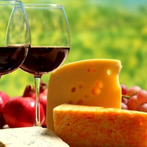 a lovely arrangement of red wine and cheeses with grapes in the background