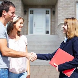 a young couple closes a deal with a handshake with their realtor