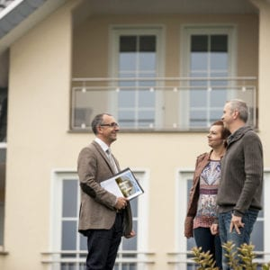 a male realtor speaks with a middle-aged couple in front of a house they are interested in