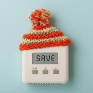 """Thermostat with the word """"SAVE"""" on screen and a small winter hat on top."""