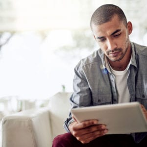 Young man in casual clothing reading a tablet in a bright room