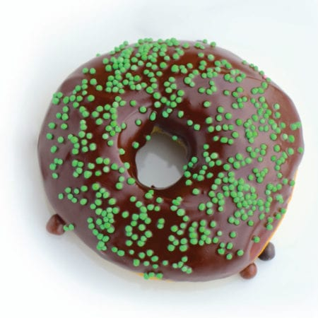 Donut with chocolate icing and green sprinkles